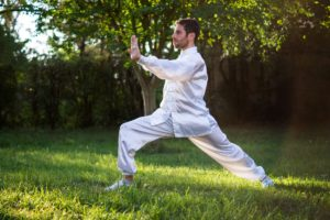 Doing thai chi in park - avoid stress when moving