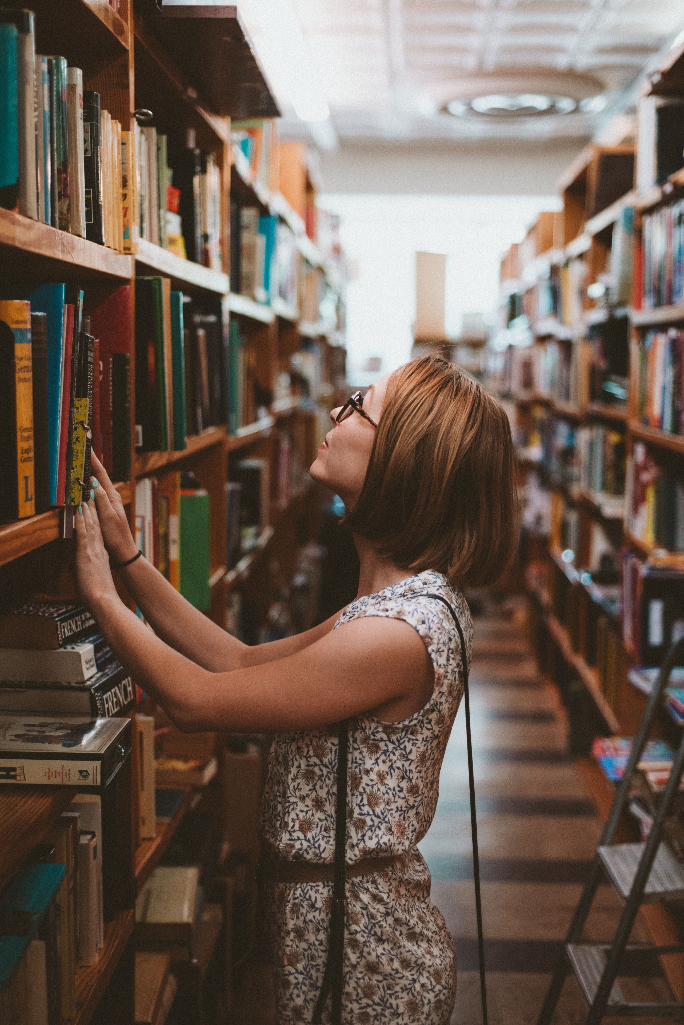 a woman in a library looking for a book