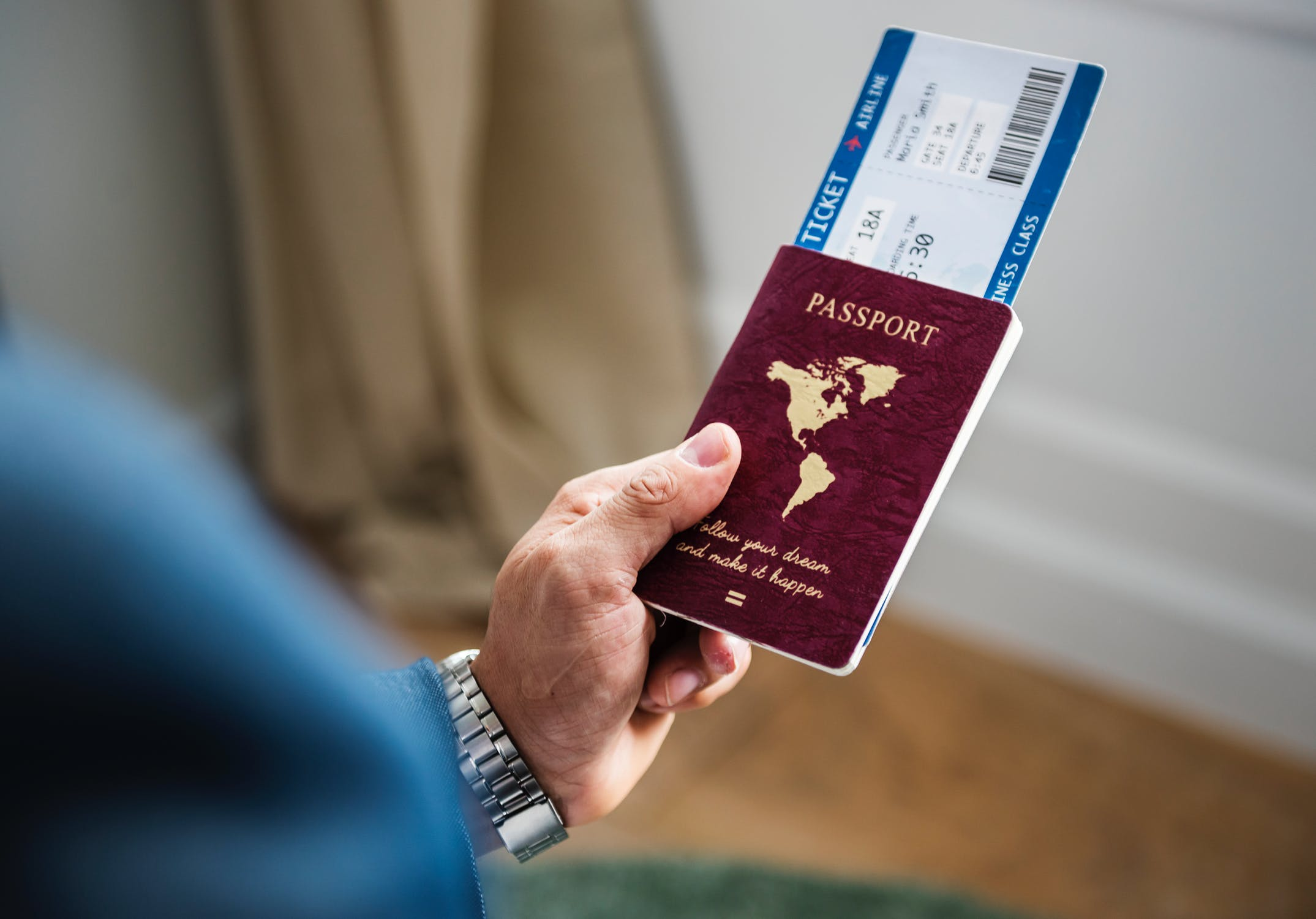 Man holding a passport and an airplane ticket