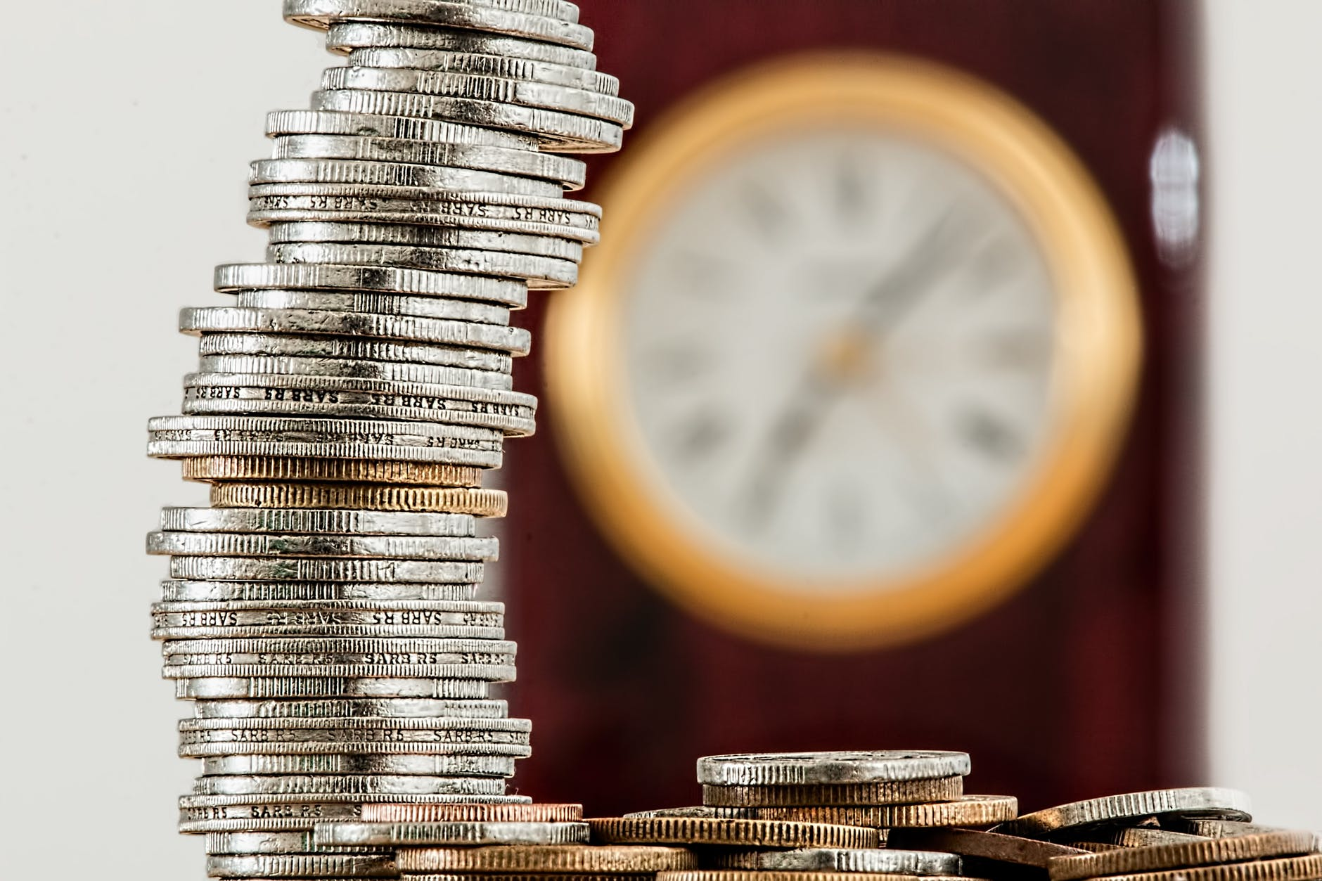 a stack of coins in front of a clock