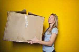 A girl holding a cardboard box while trying to settle down after the move