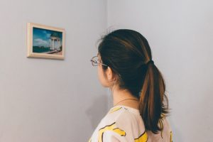 A woman looking at a picture ina frame on the wall.
