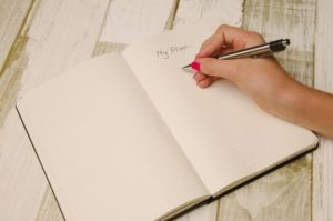 A woman writing her plan in a notebook after considering all the benefits of moving to Los Angeles.