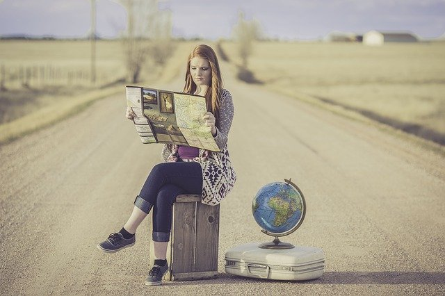 A woman sitting on her suitcase on the middle of the road with a globe and a map in her hands.