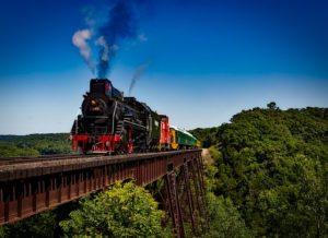 A train leaving a steam trail crossing the bridge.