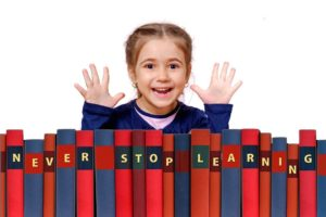 Happy little girls standing above stacked books that together spell out the phrase never stop learning.