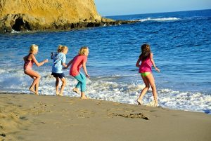 Kids playing at beach in one of the best places to buy a house in Orange County