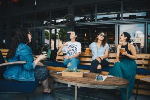 There are four girls sitting in a cafe chatting and laughing, since meeting new and different people is one of the benefits of living in Diamond Bar.