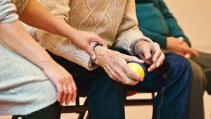 An elderly man holding a stress ball.