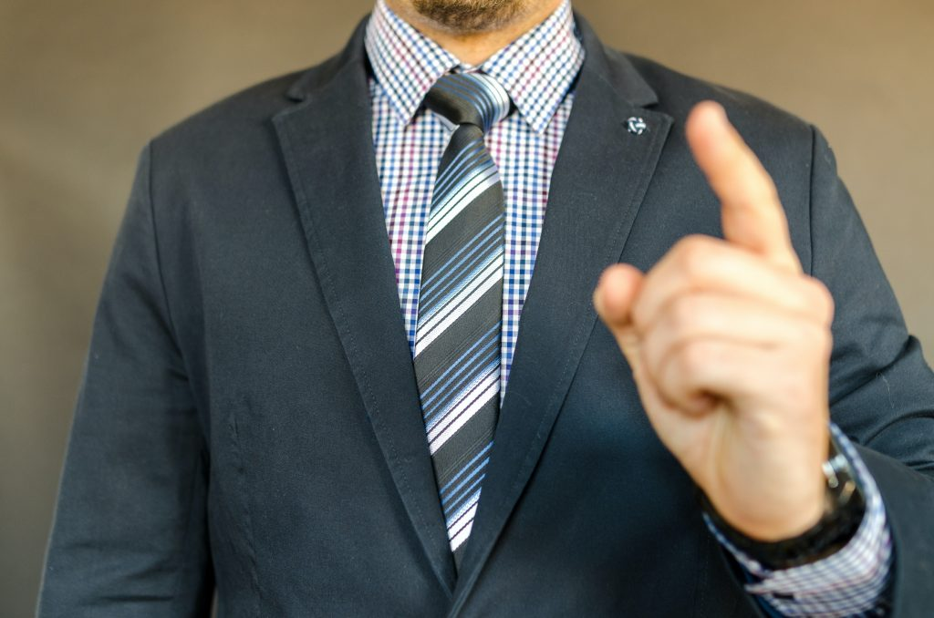 man in a suit holding raised finger