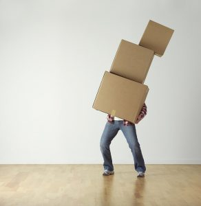 A man carrying a pile of moving boxes.