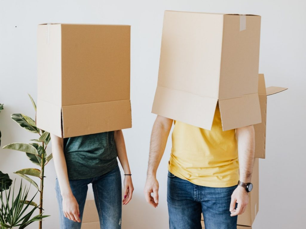 Two people with moving boxes over the head.