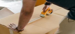 A man taping a cardboard box after packing.