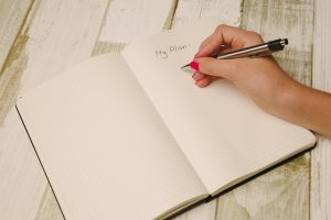A female hand writing getting ready to write down a plan in a notebook.