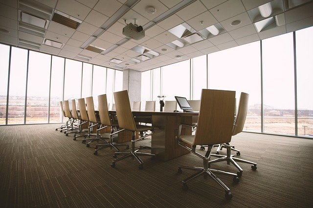 A conference room with many chairs around an office.