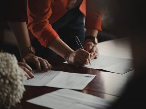 Two people signing a contract.