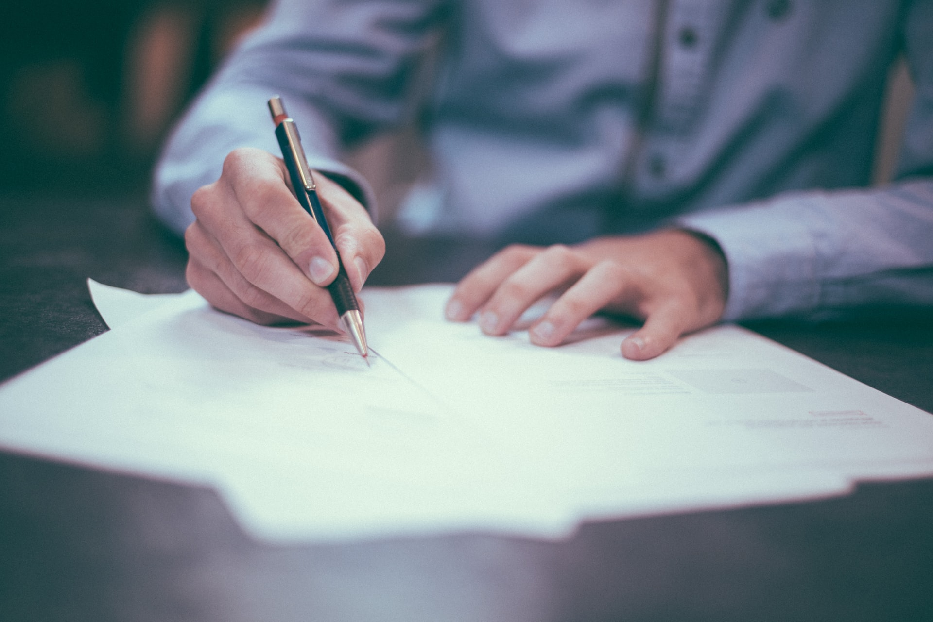 A man signing a contract. It's good to know some basic moving contract terms.