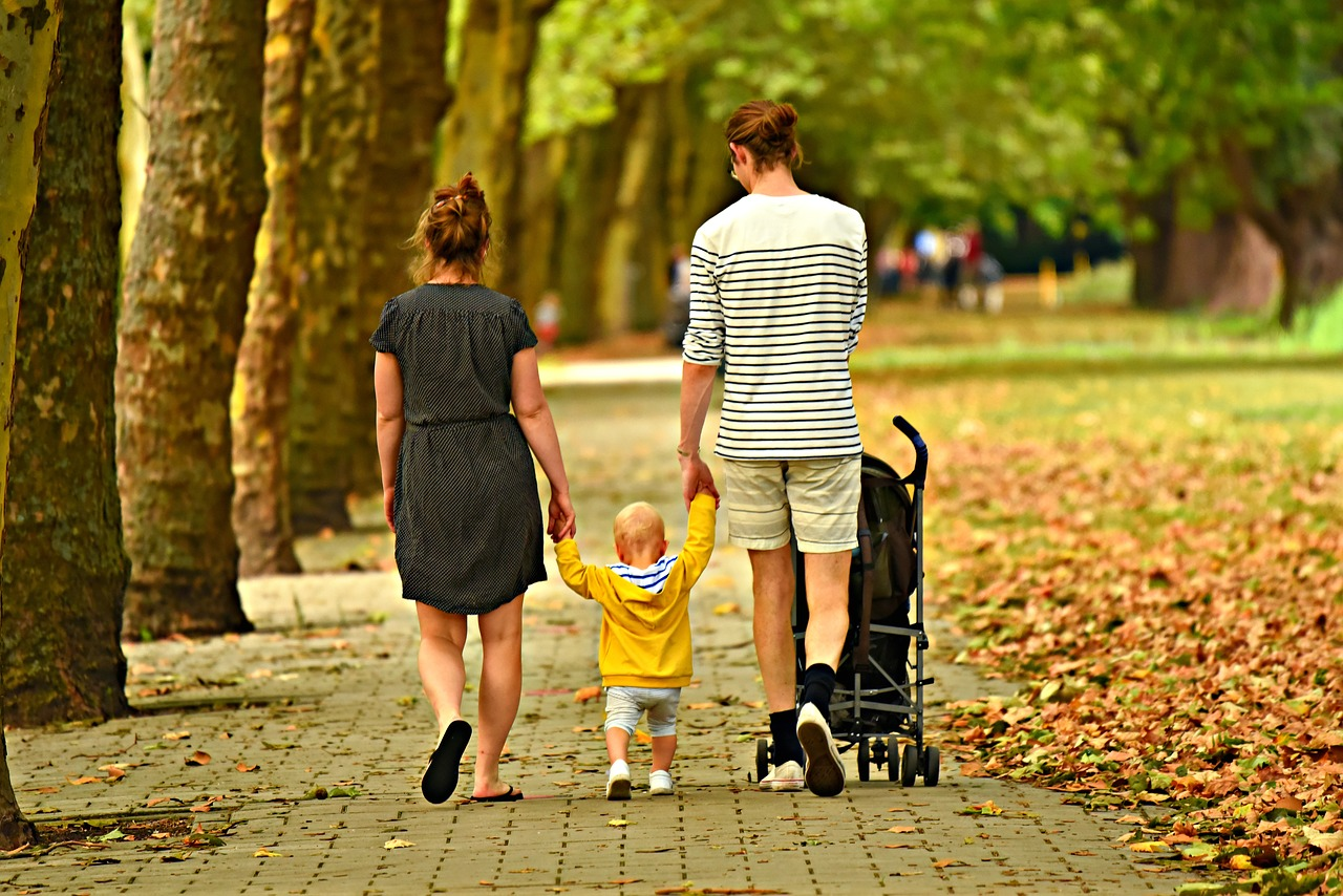 Parents walking their child in the park and discussing the top family-friendly cities in Canyon County.