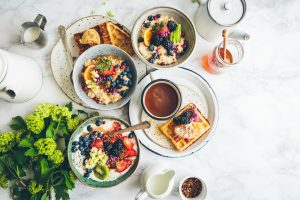 Plates filled with various foods on a table. Renting an apartment in Astoria will guarantee you try some of the best food in NYC.