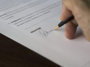A man signing a contract before leaving the States,