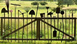 Gardening tools hung on the gate, an example of how to store garden tools