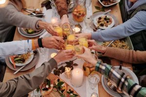 A group of people toasting over food.