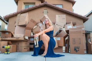 A woman sitting with a wine bottle in her hand, in front of moving boxes.