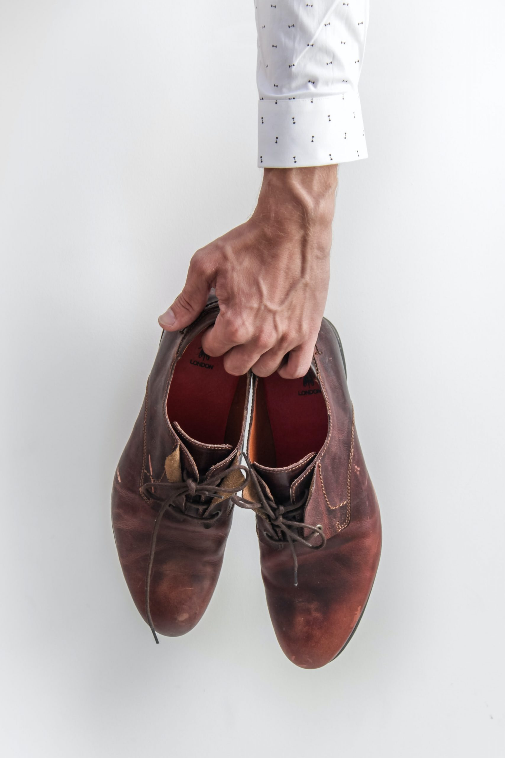 A person holding a pair of shoes.