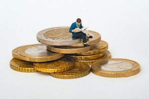 A miniature of a man sitting on coins